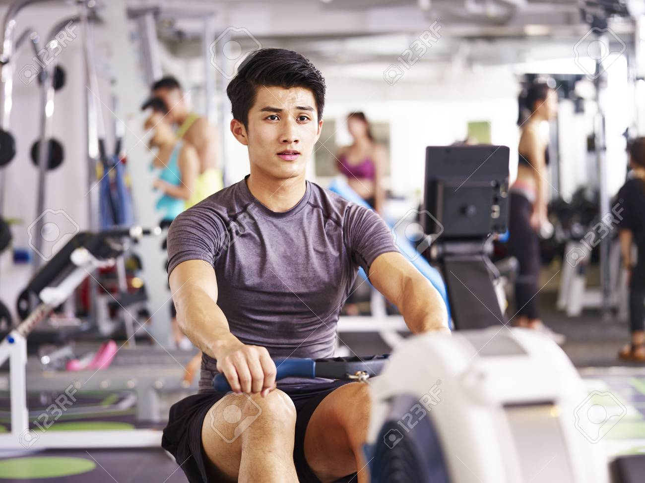 young asian adult man working out in gym using rowing machine. - 87617758