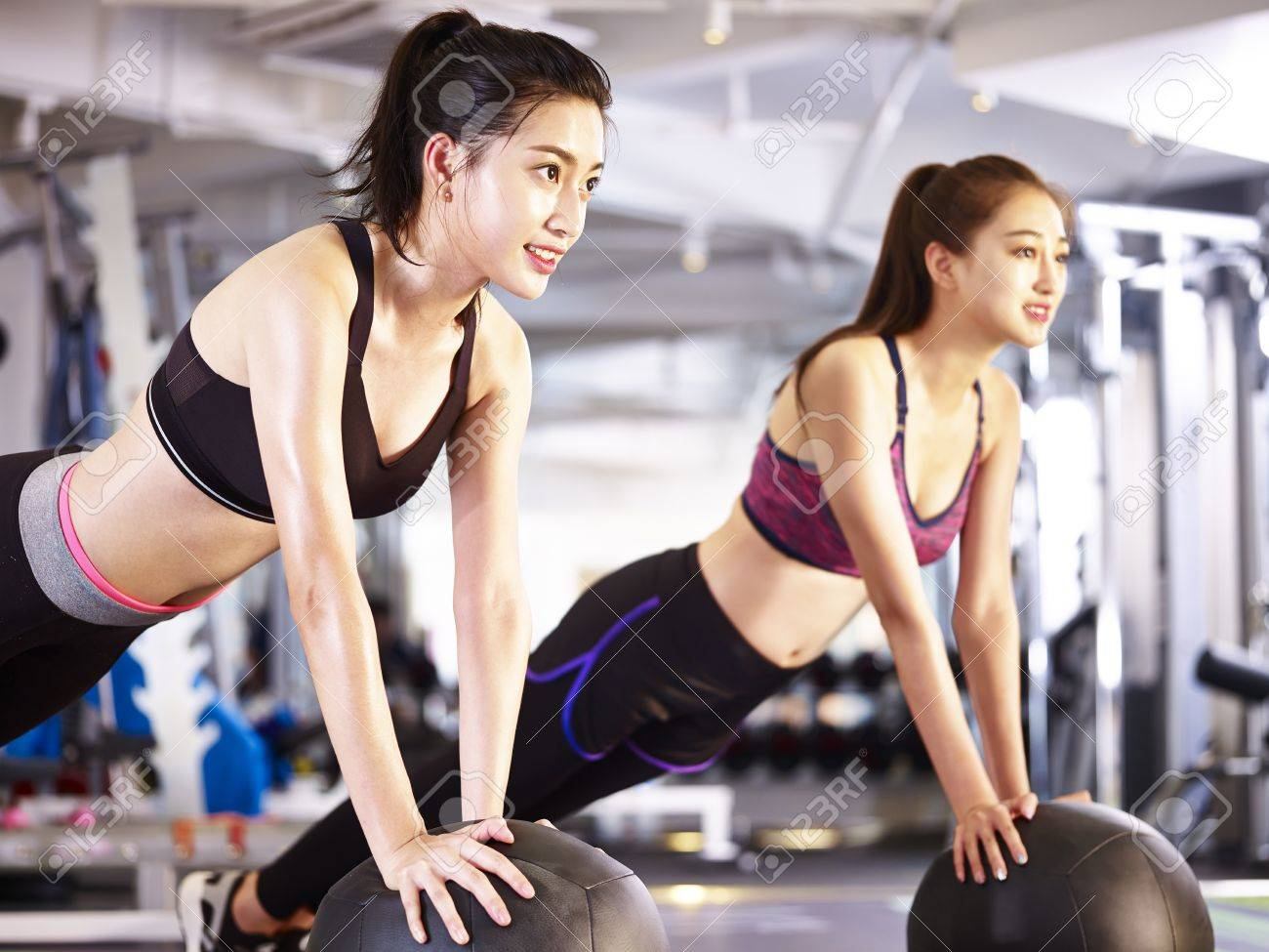 two young asian adult women working out in gym using medicine balls. - 87617764