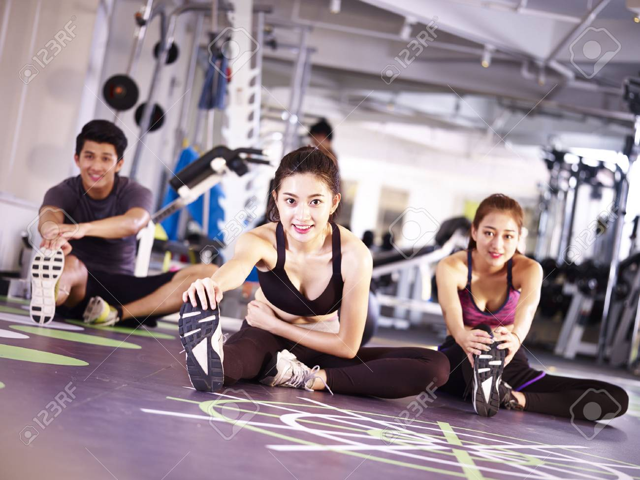 three young asian adult people exercising in gym stretching legs. - 87617765