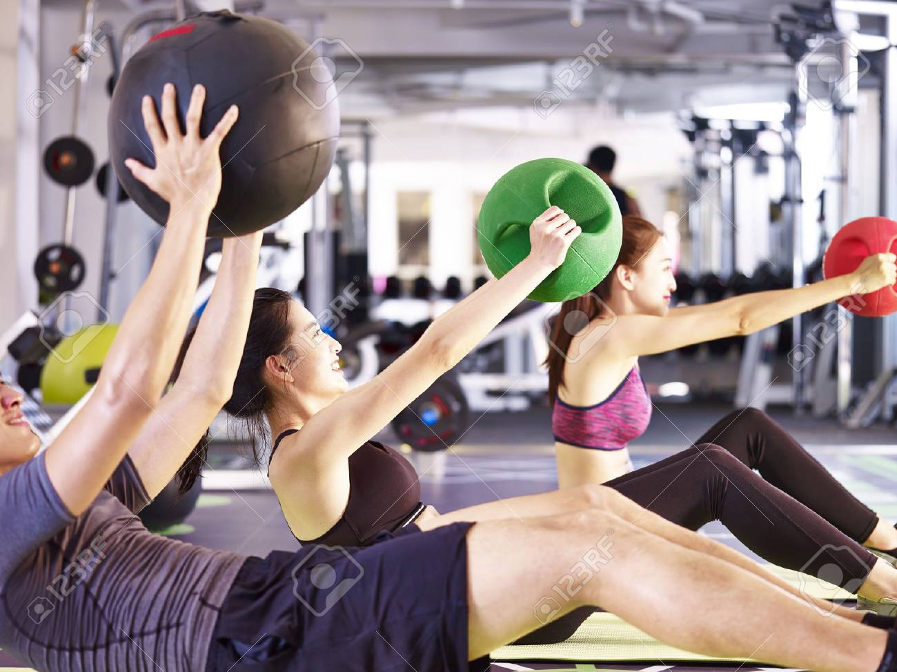 three young asian adult people working out in fitness center using medicine balls. - 87617766