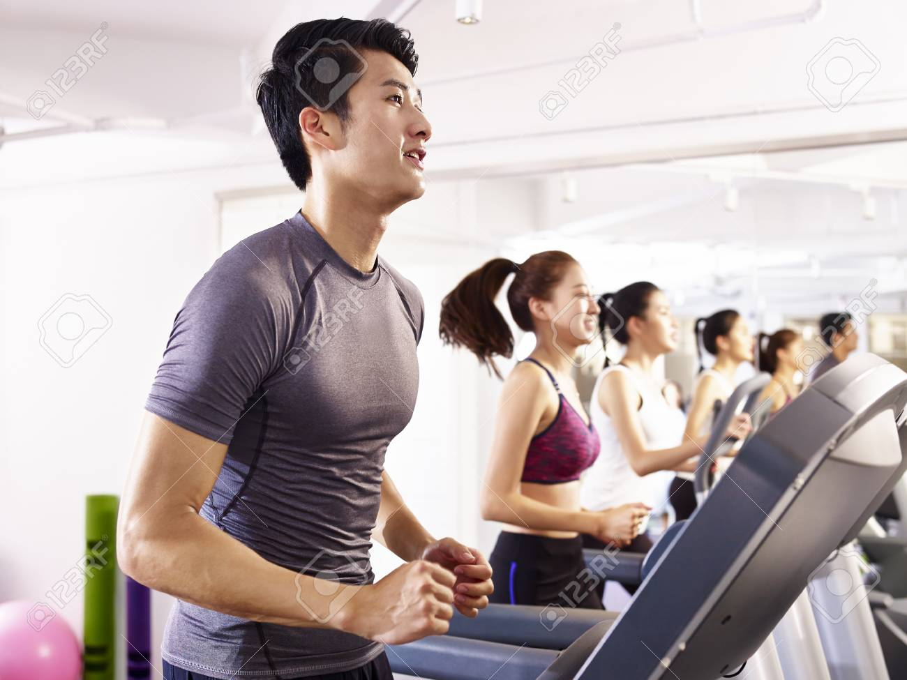young asian adult working out on treadmill. - 88030786