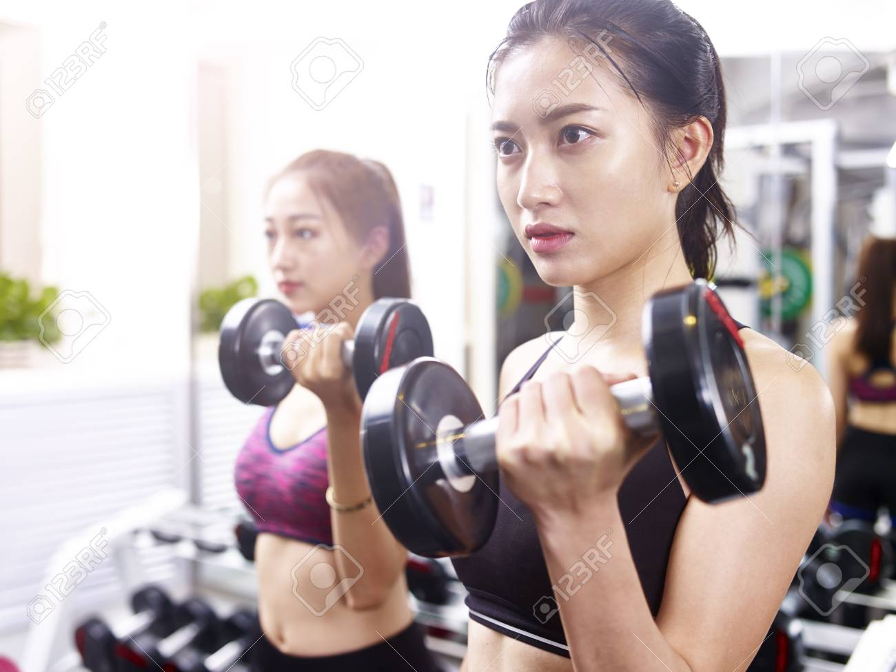 two young asian women working out exercising in gym using dumbbells. - 89328939