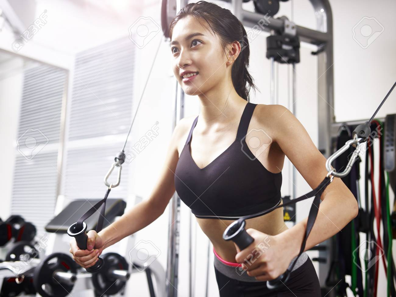 young asian woman working out in gym using exercising equipment. - 89328921