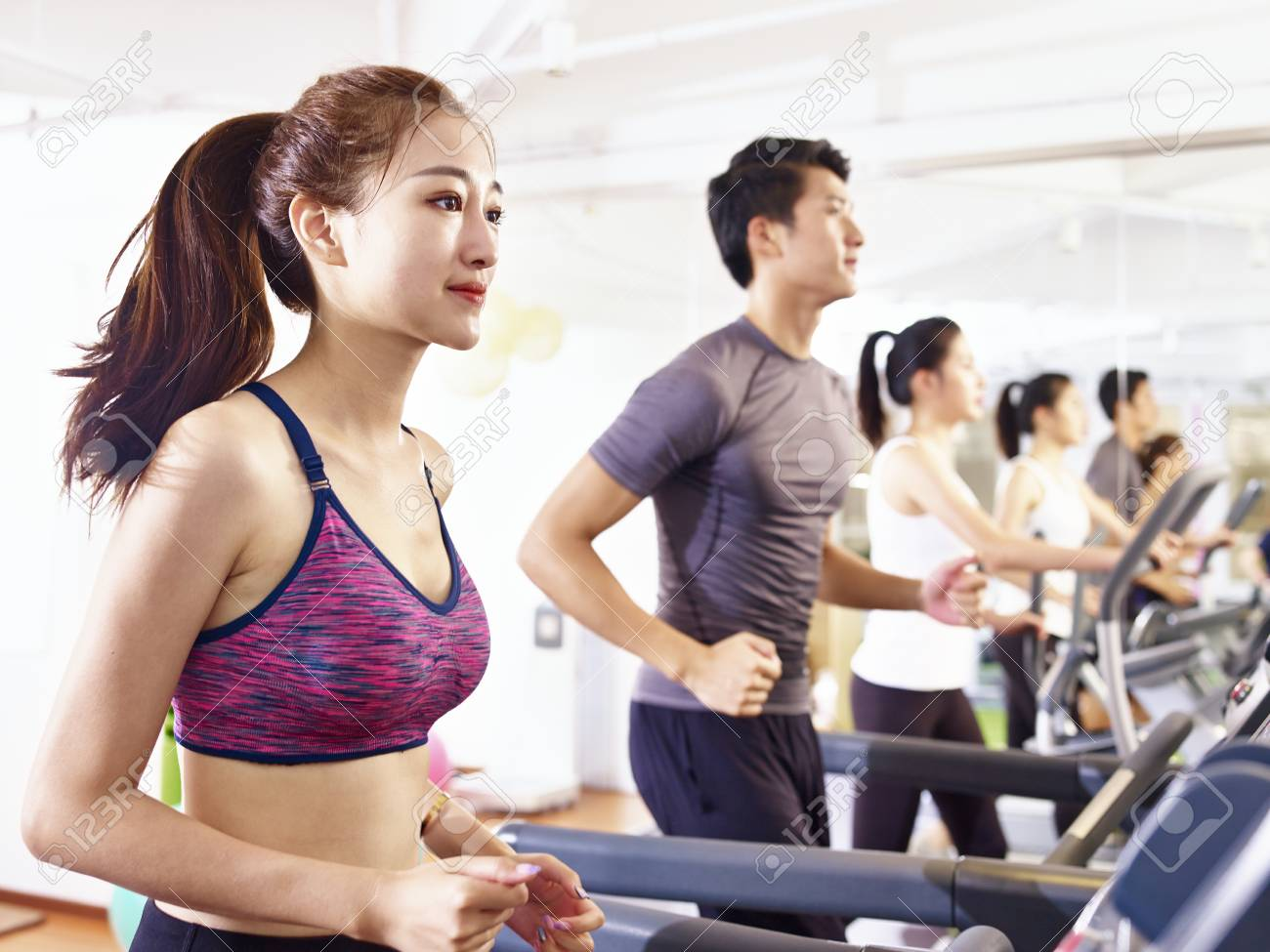 young asian adult working out on treadmill. - 90955897