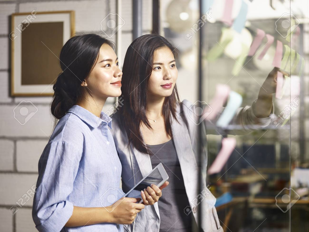 two young asian women entrepreneurs discussing business plan in office using sticky notes. - 90955902