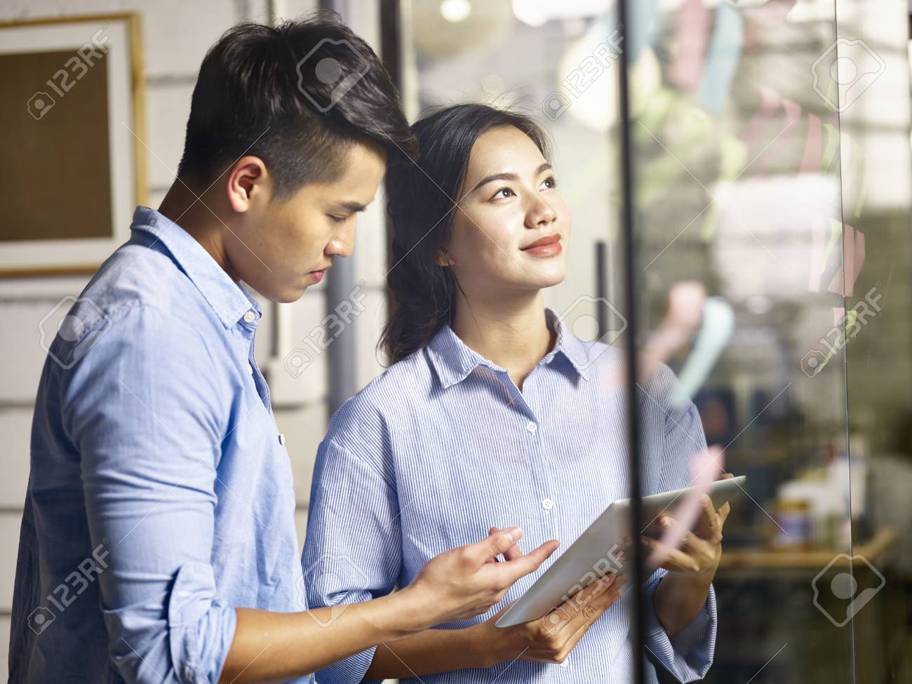 young asian businessman and businesswoman working together making a business plan using adhesive notes in office. - 91431254