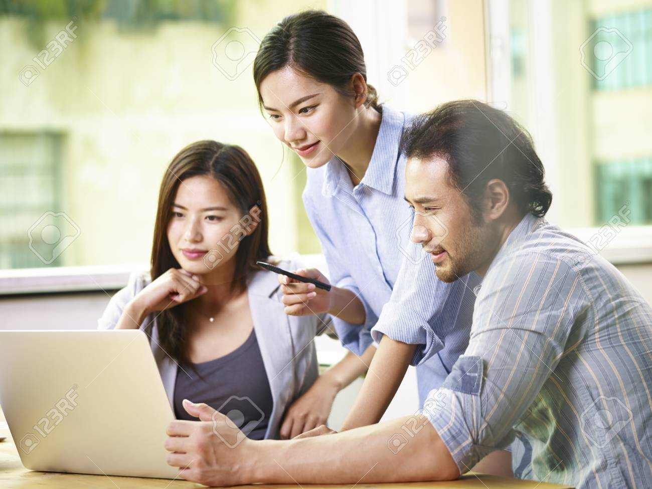 team of young asian business people in casual wear working together in office using laptop computer. - 91514228