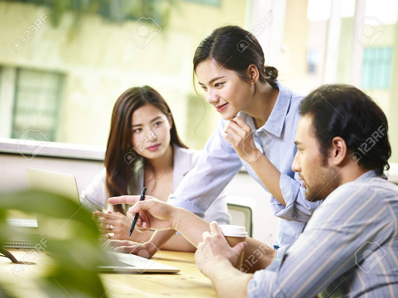 team of young asian business people in casual wear working together in office using laptop computer. - 91514231