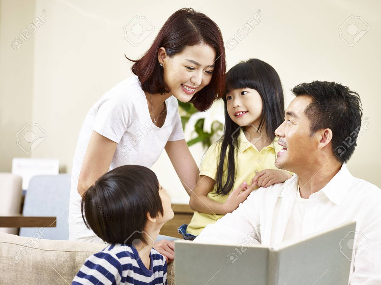 asian parents mother and father and two children son and daughter reading a book telling a story together. - 91878561