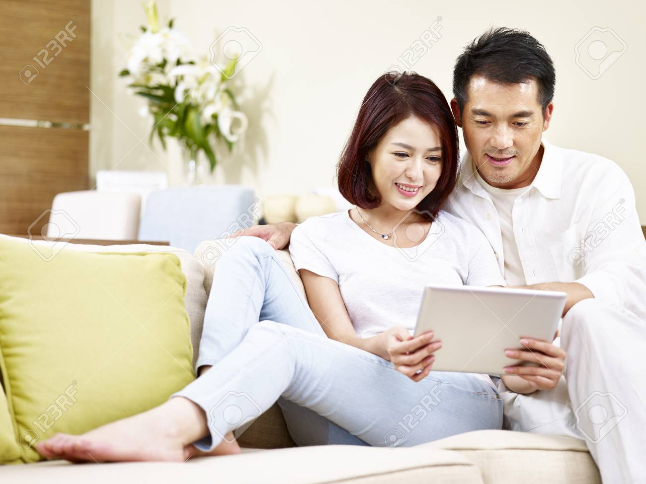 asian couple sitting on family couch in living room using digital tablet together. - 91879462