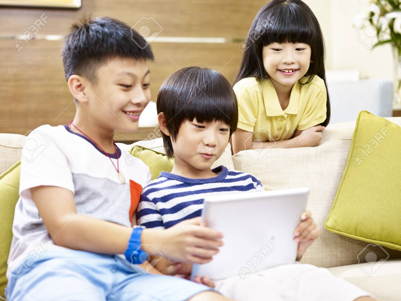 three asian children two little boy and one little girl sitting on couch at home playing video game with digital tablet, focus on the little girl in the back. - 92267957