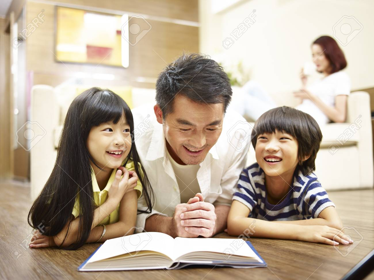 asian father and two children lying on front on floor reading book while mother relaxing in the background. - 92269479