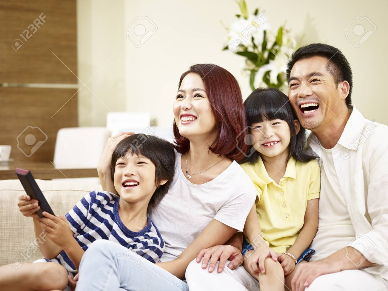 happy asian family with two children sitting on couch at home watching TV. - 92705705