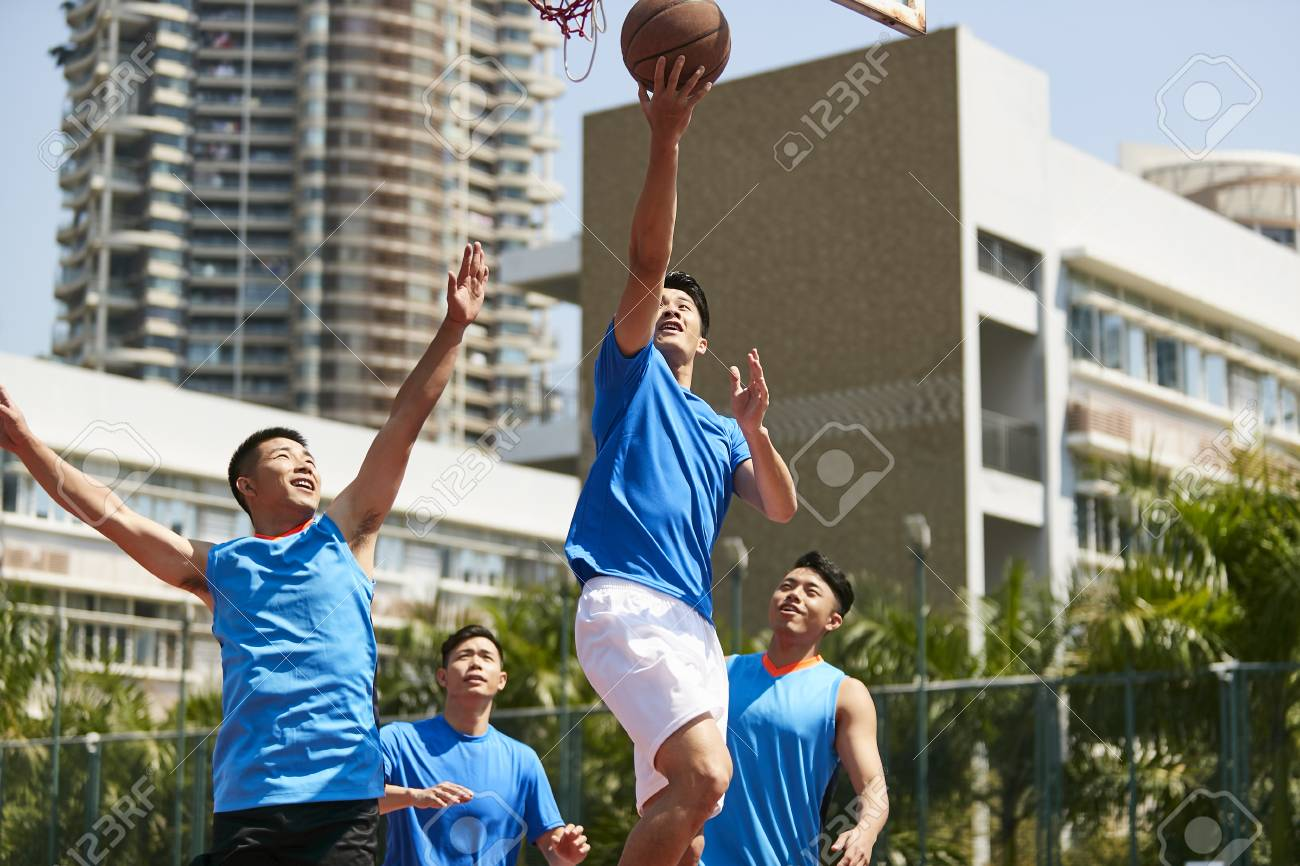 young asian adult male player playing basketball on a urban outdoor court. - 103906546