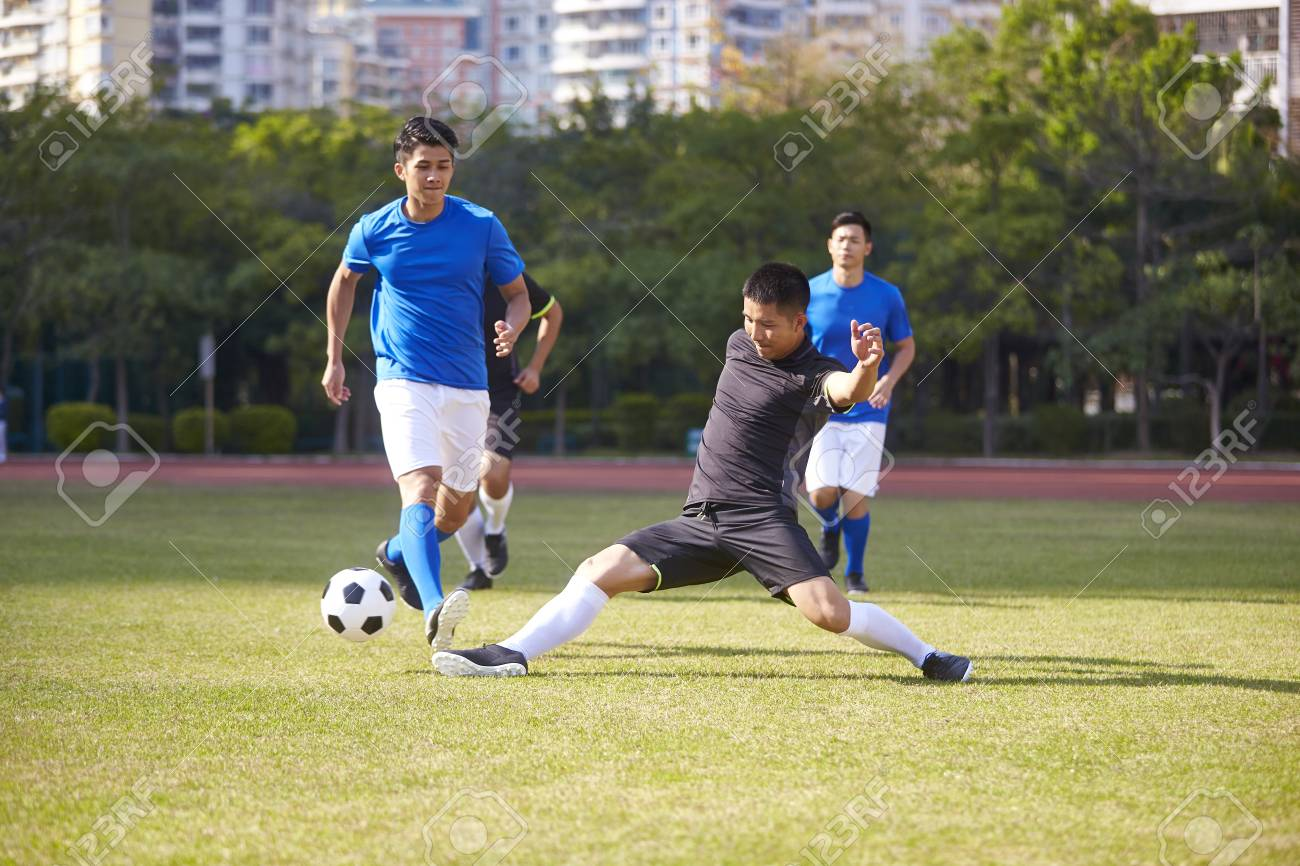 a group of young asian soccer football player playing on outdoor court. - 112315686