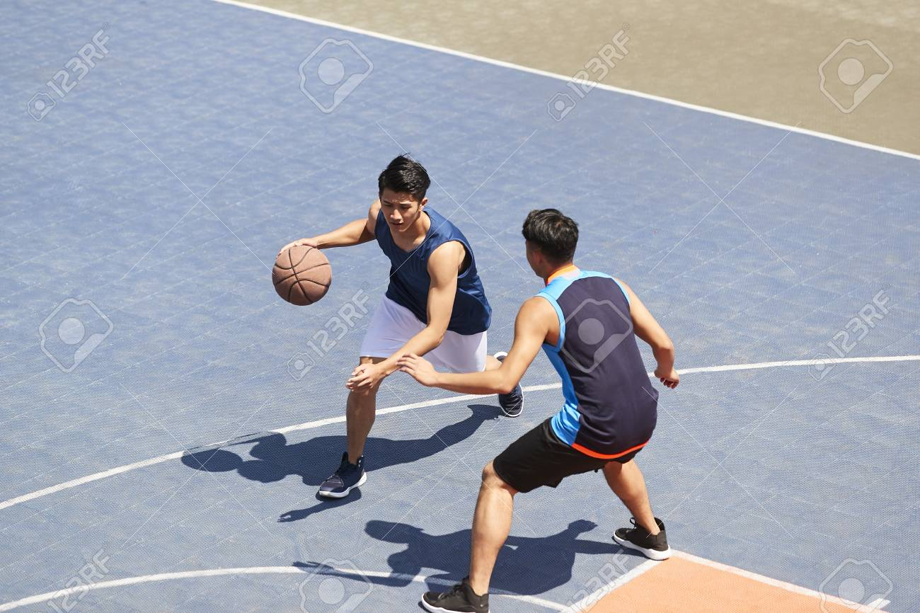 two young asian basketball players playing one on one on outdoor court. - 113197321