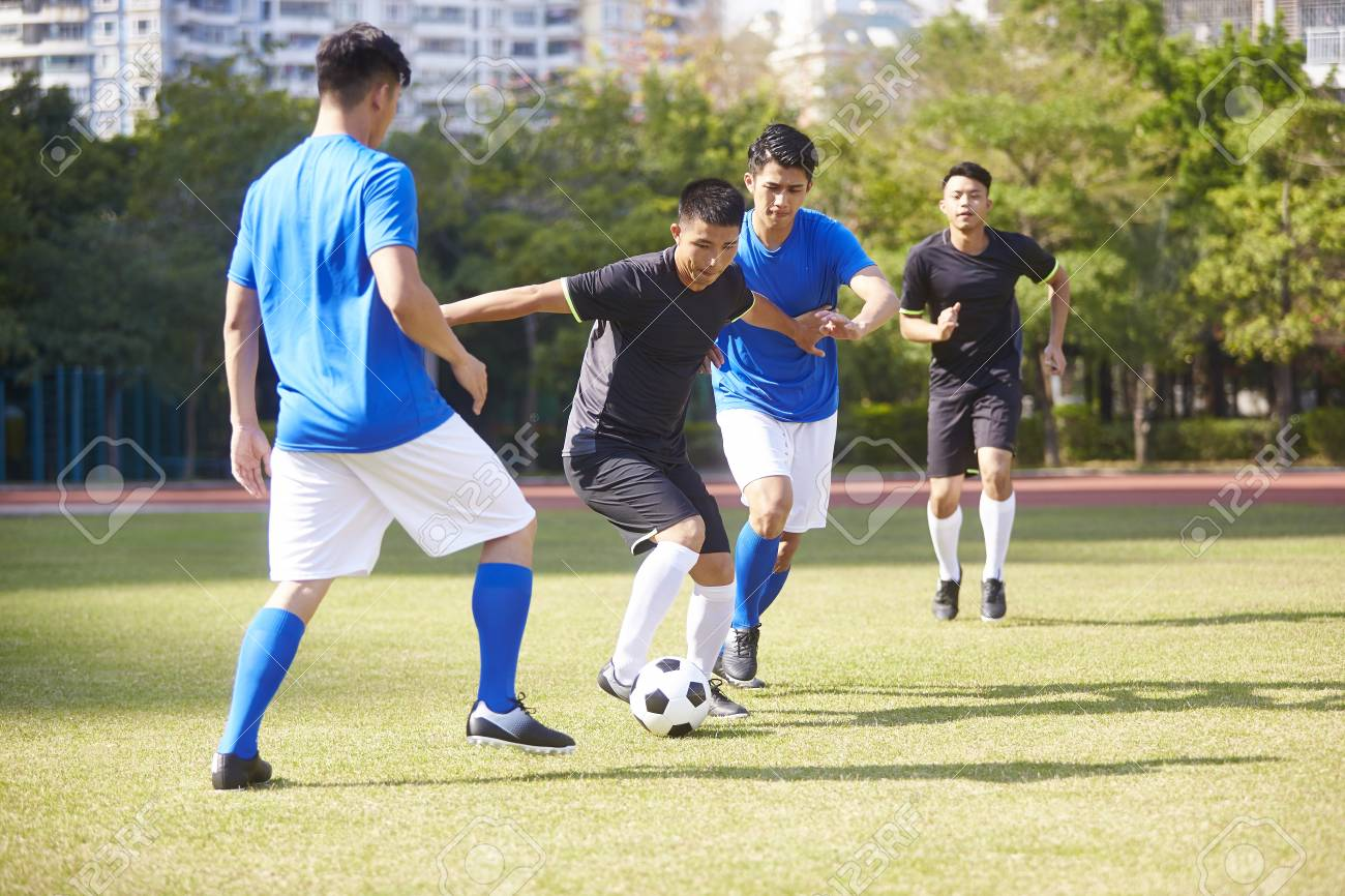 a group of young asian soccer football player playing on outdoor court. - 113433854