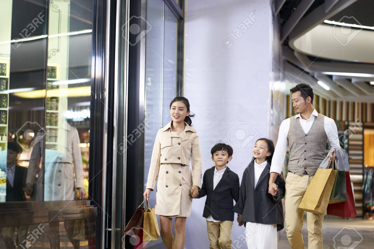 happy asian family with two children walking in shopping mall - 115866245