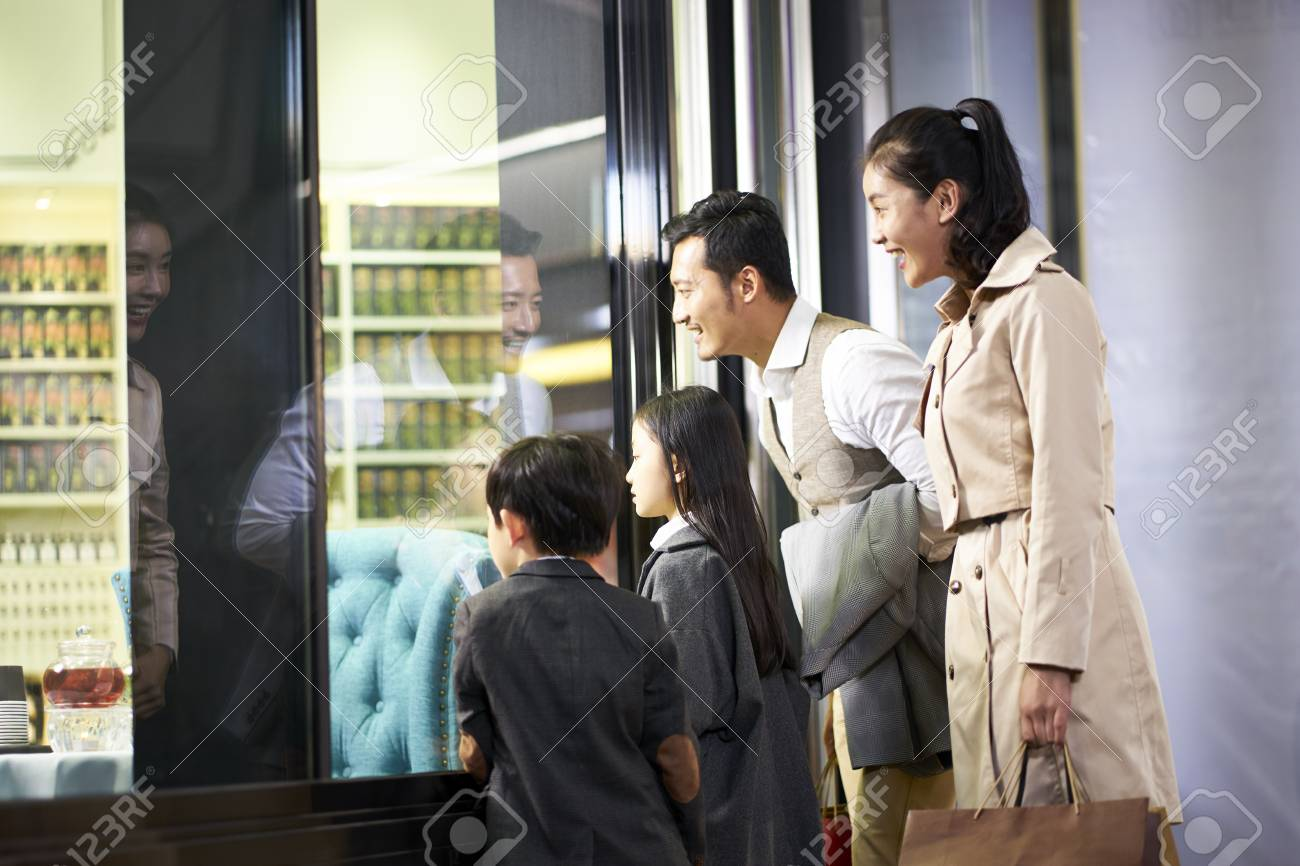 happy asian family with two children looking into a shop window in shopping mall - 115866247