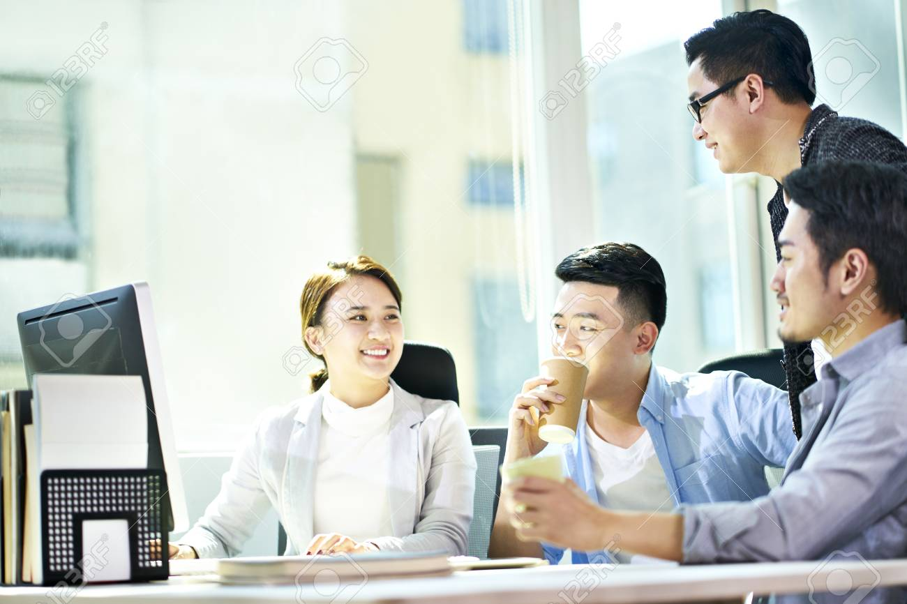 four young asian businesspeople meeting in office discussing business plan using tablet PC. - 119594997