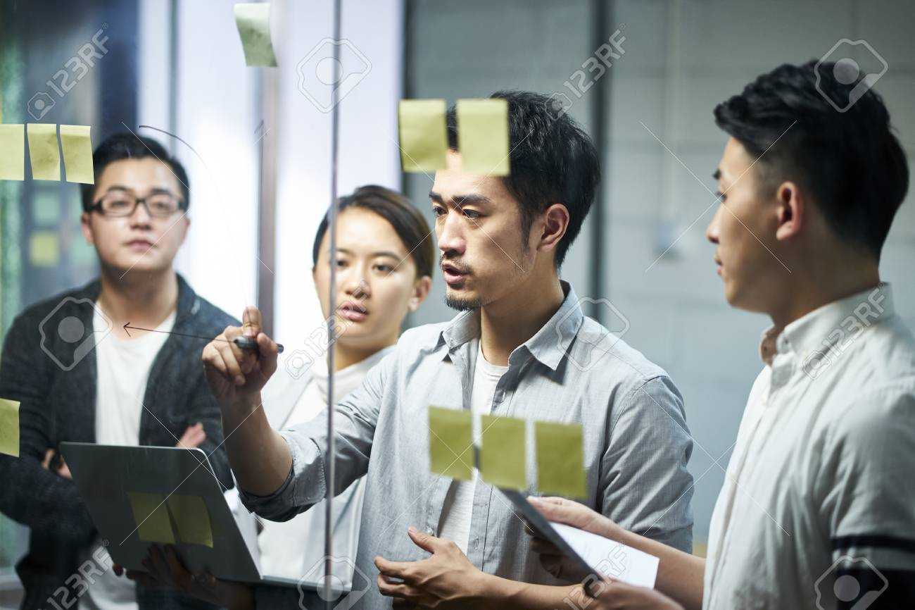 young asian entrepreneur of small company drawing a diagram on glass during team meeting discussing and analyzing business situation in office. - 120405597