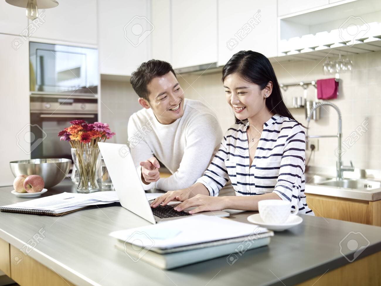happy young asian couple working together from home talking discussing using laptop computer in kitchen - 132281657