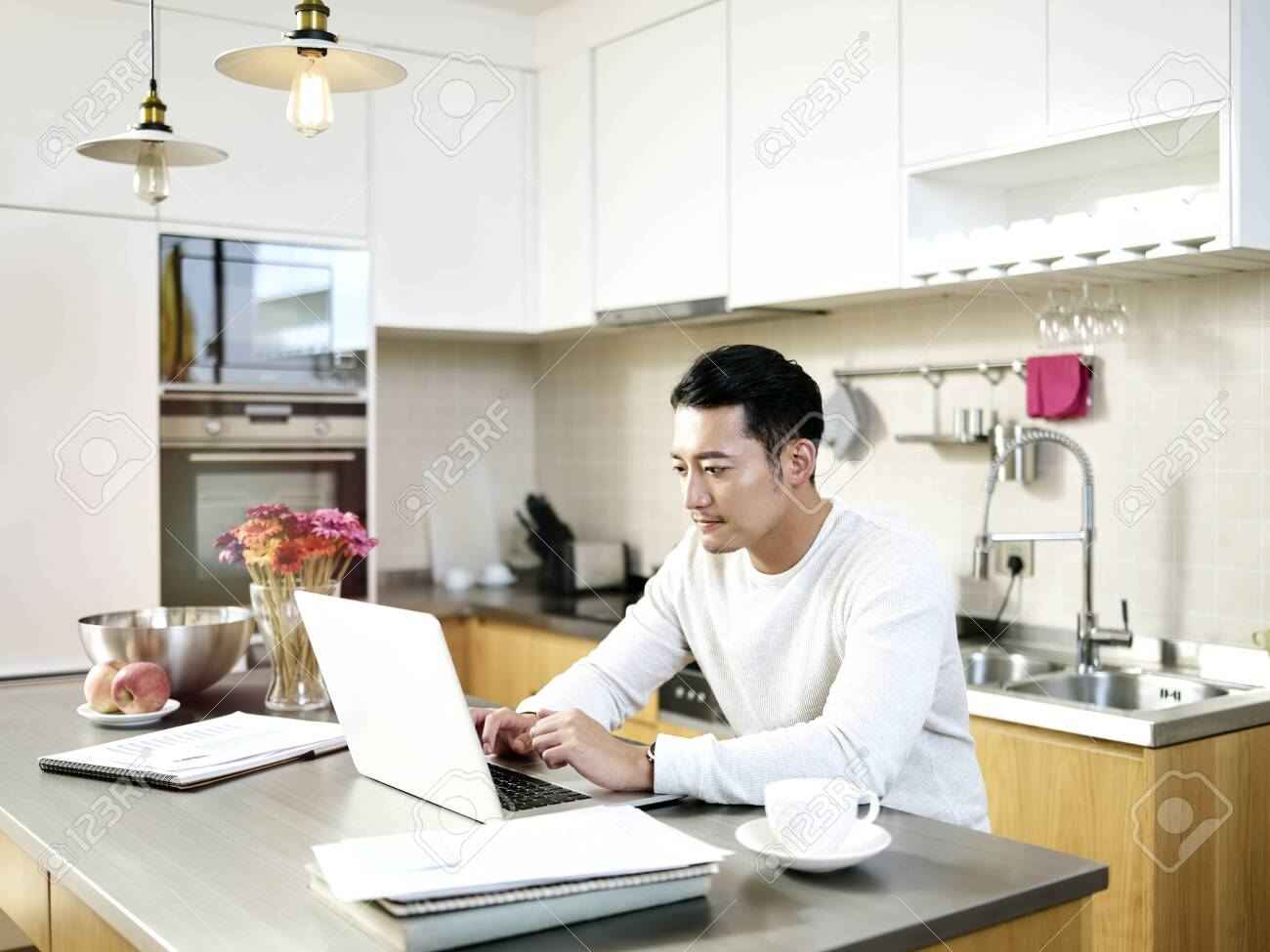 young asian man working from home sitting at kitchen counter using laptop computer - 132759870