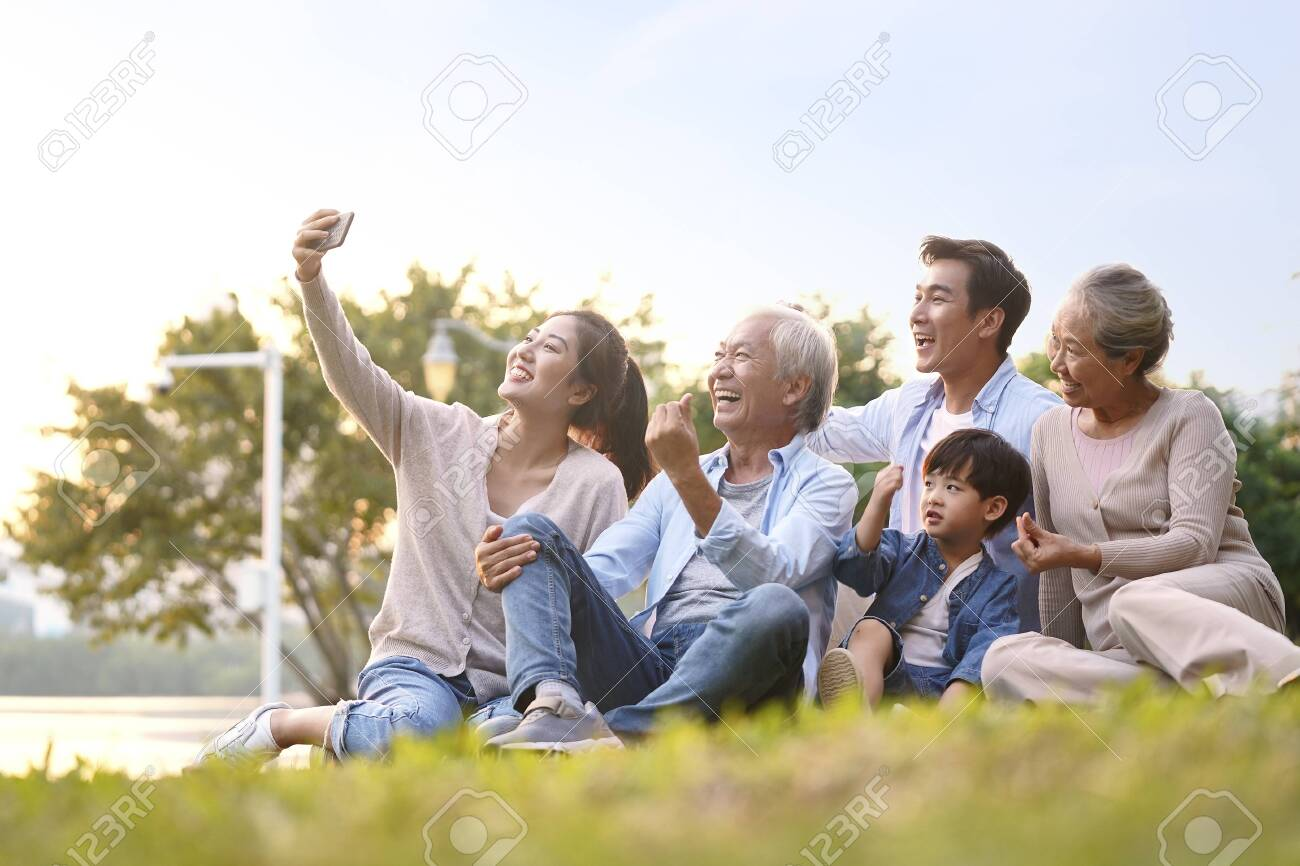 three generation happy asian family sitting on grass taking a selfie using mobile phone outdoors in park - 134199050