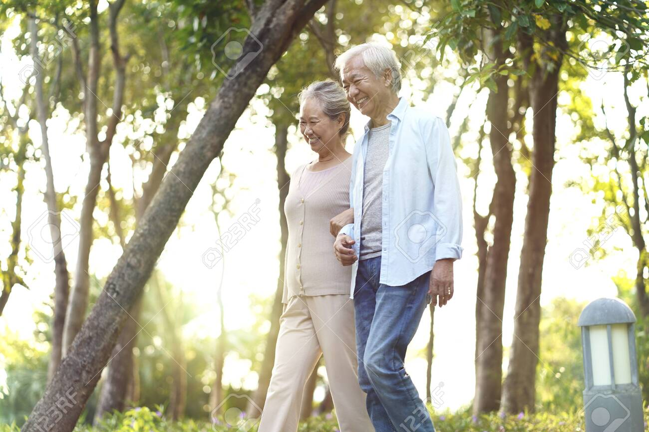 happy senior asian couple walking talking relaxing outdoors in park - 134270367
