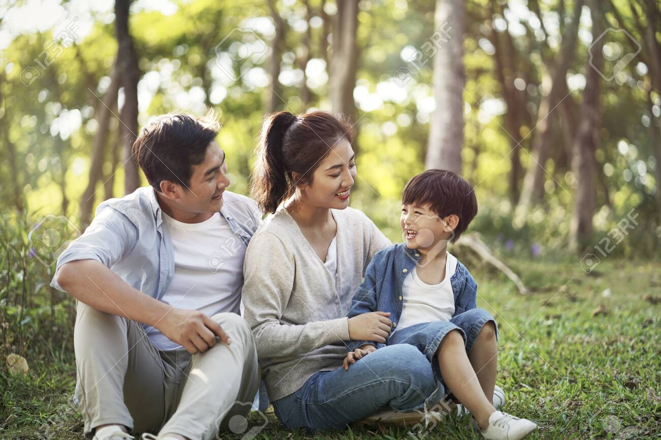 young asian parents and son having fun outdoors in park - 135461880