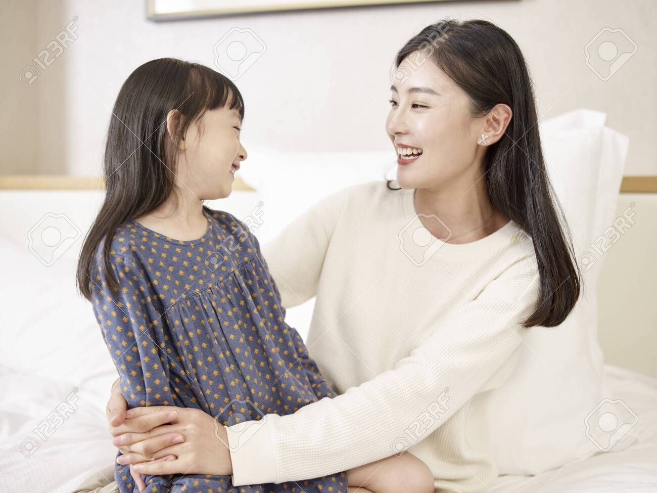 young asian mother and elementary age daughter sitting in bed relaxing playing chatting at home - 146178444