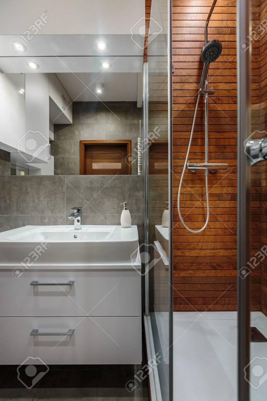 Luminoso cuarto de baño moderno con muebles blancos y la pared de madera