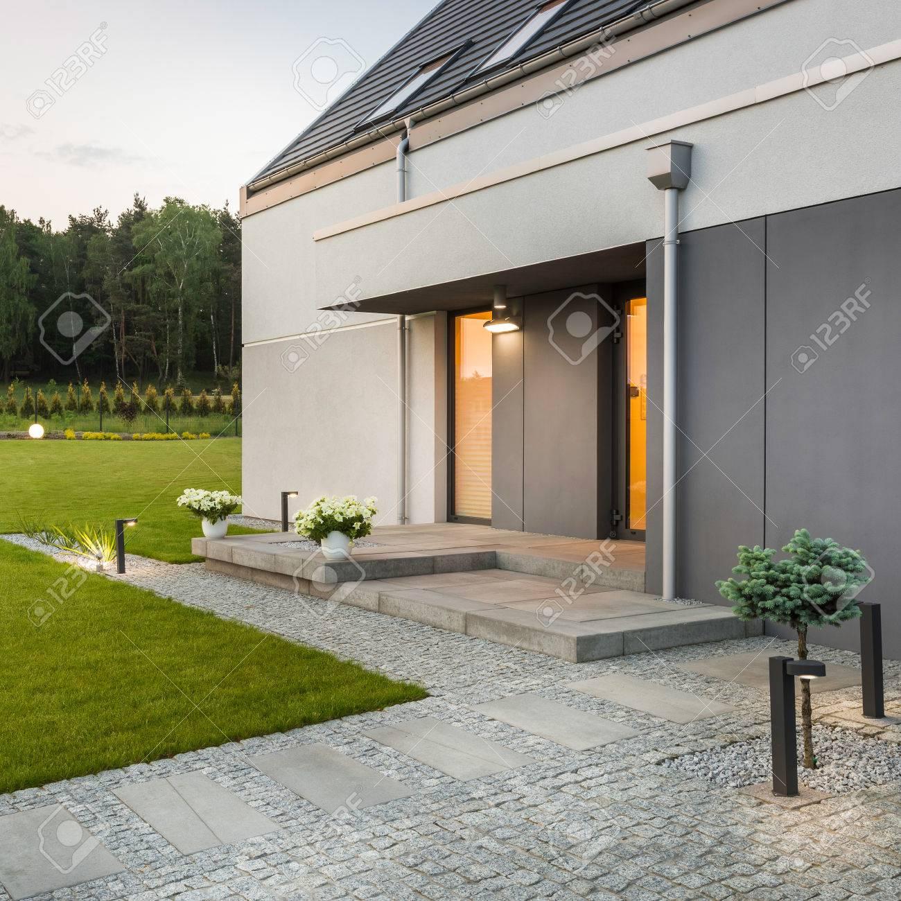 Maison moderne avec jardin simple et éclairage extérieur décoratif