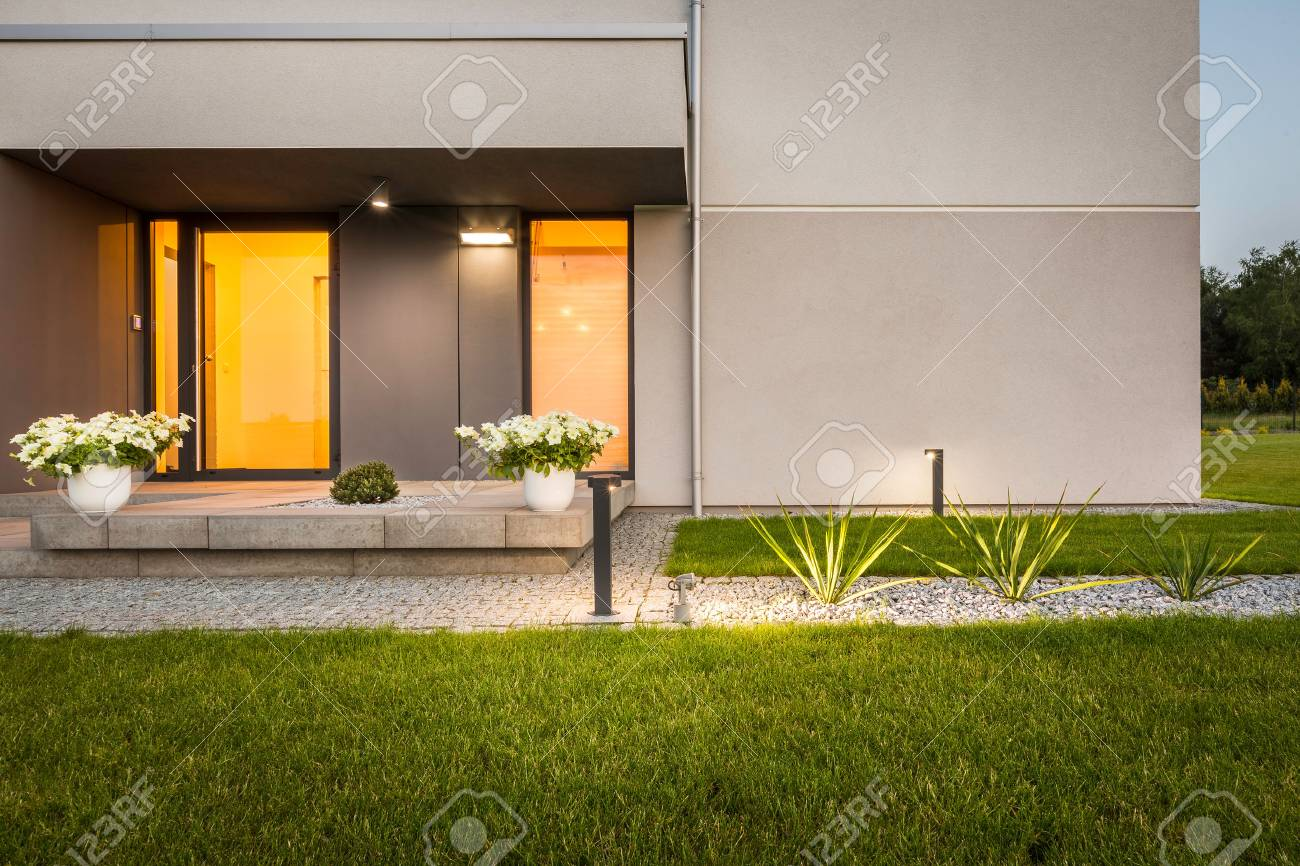 Maison contemporaine avec jardin et éclairage décoratif extérieur, vue  extérieure