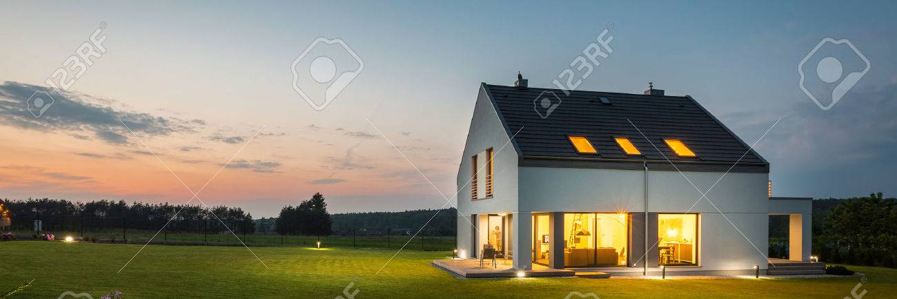 Panoramic photo of modern house with outdoor and indoor lighting, at night - 59566434