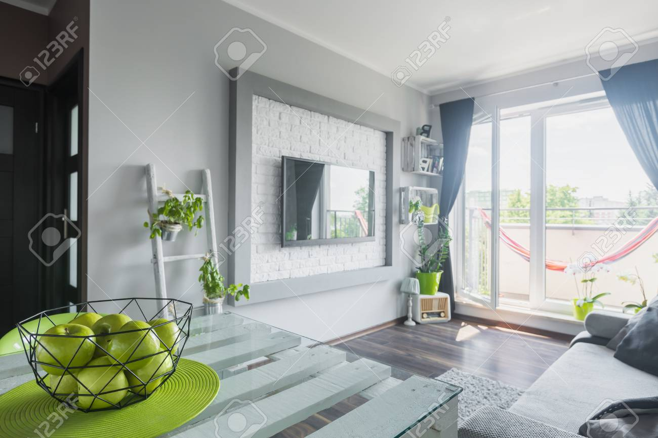 Light Living Room With White Wooden Table, Sofa, Big Tv And Balcony ...