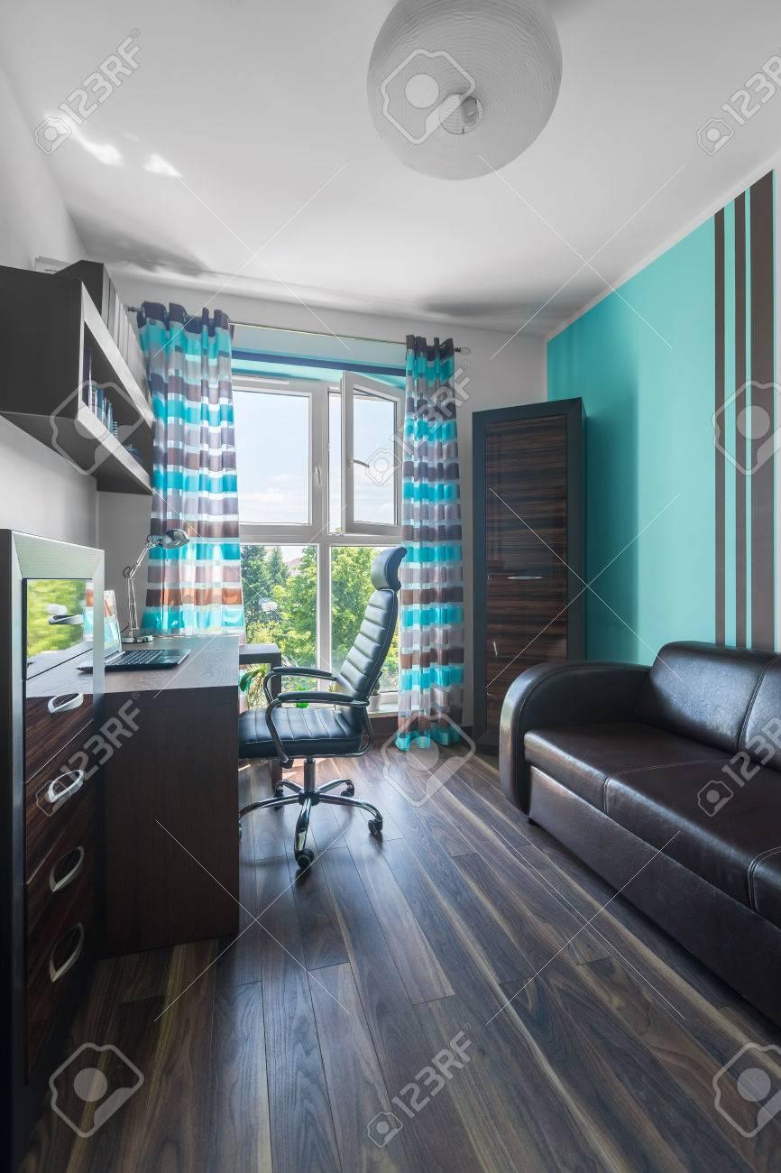 Chambre spacieuse en marron et turquoise avec des meubles en bois, un  canapé en cuir et un fauteuil