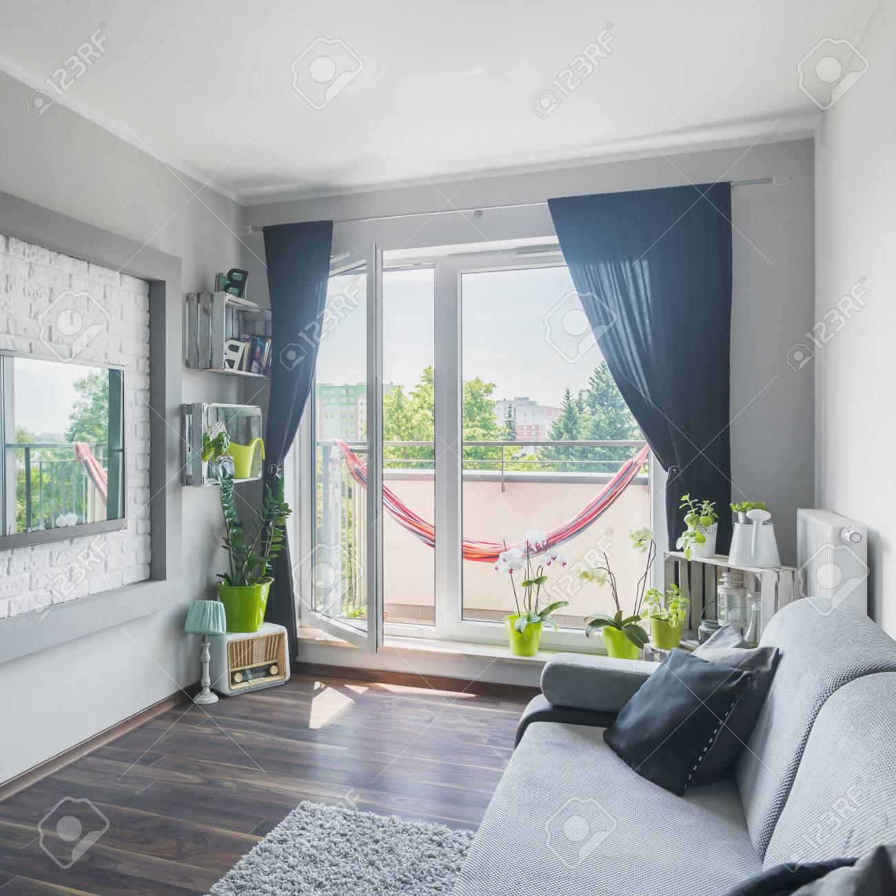 Schöne Wohnzimmer Interieur Mit Sofa, Großer Fernseher, Dekorative Wände,  Holzboden Und Balkon Standard