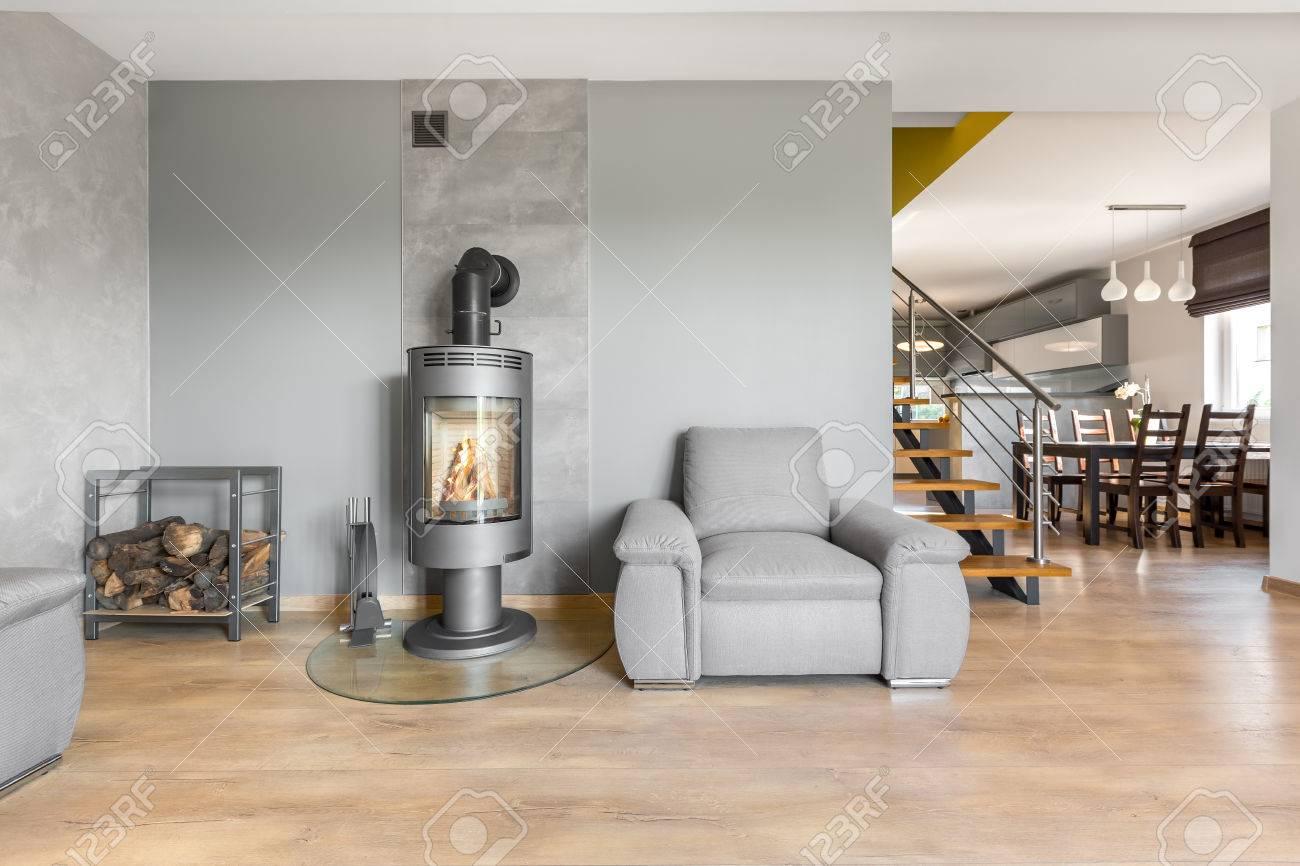 Geräumiges Wohnzimmer Mit Sessel, Kamin Im Industriellen Stil,  Holzbodenplatten, Treppen Und Esstisch Im