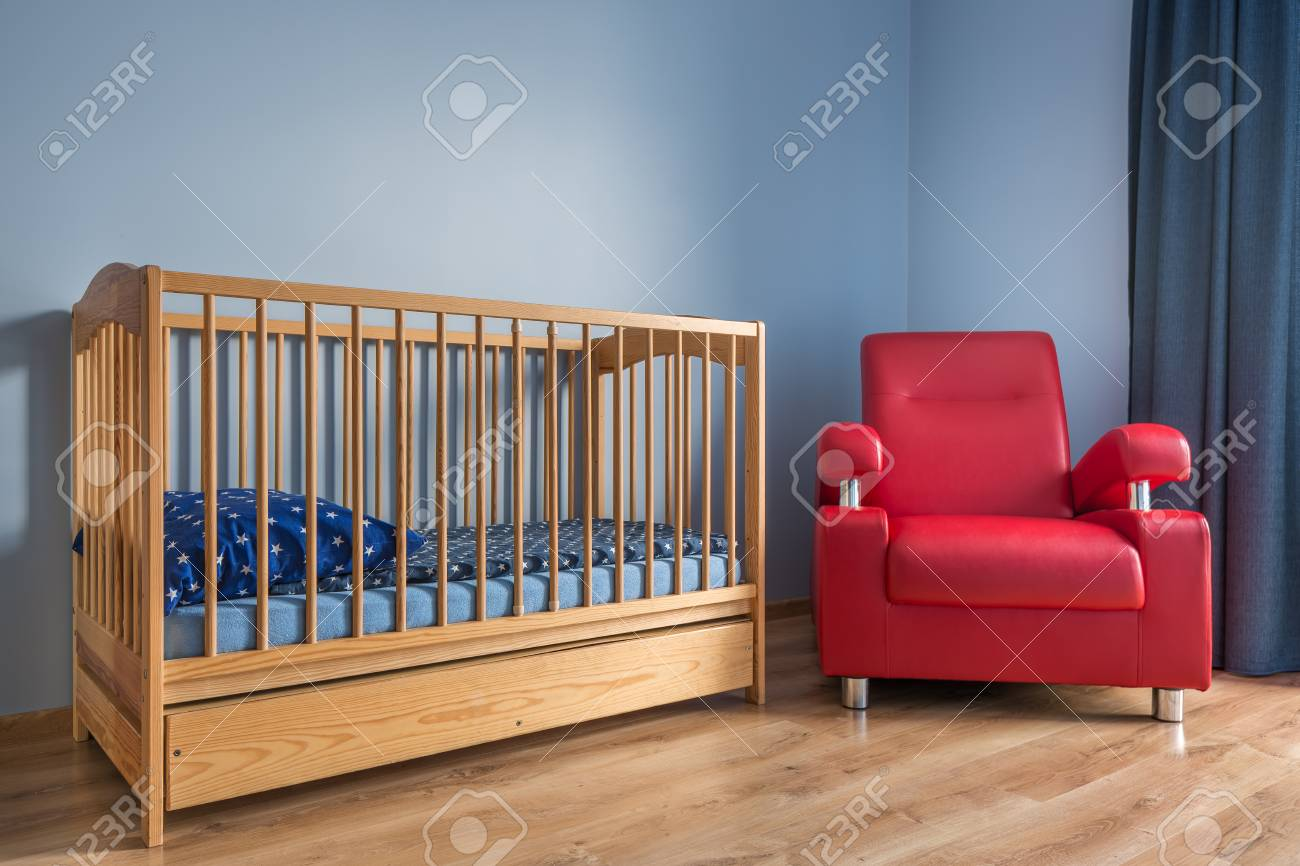 Lumière chambre de bébé bleu avec une simple lit, fauteuil rouge et du  parquet