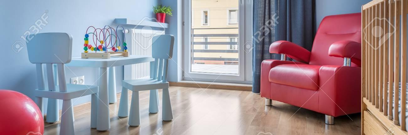 Panorama d\'une simple chambre de bébé bleu avec fauteuil rouge, pot de  fleur et la balle, lit en bois, une petite table et deux chaises
