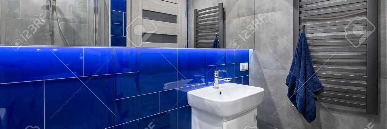 Panorama de salle de bain élégante avec meuble vasque blanc, miroir,  radiateur gris et carrelage en gris et bleu