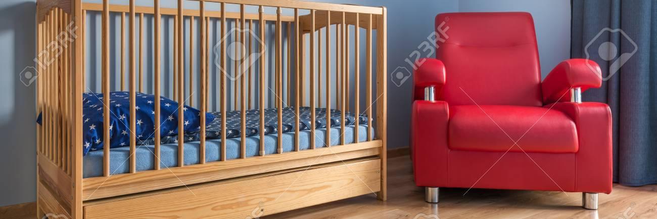 Simple chambre de bébé bleu avec lit en bois et un fauteuil rouge pour les  parents à côté de lui, panorama