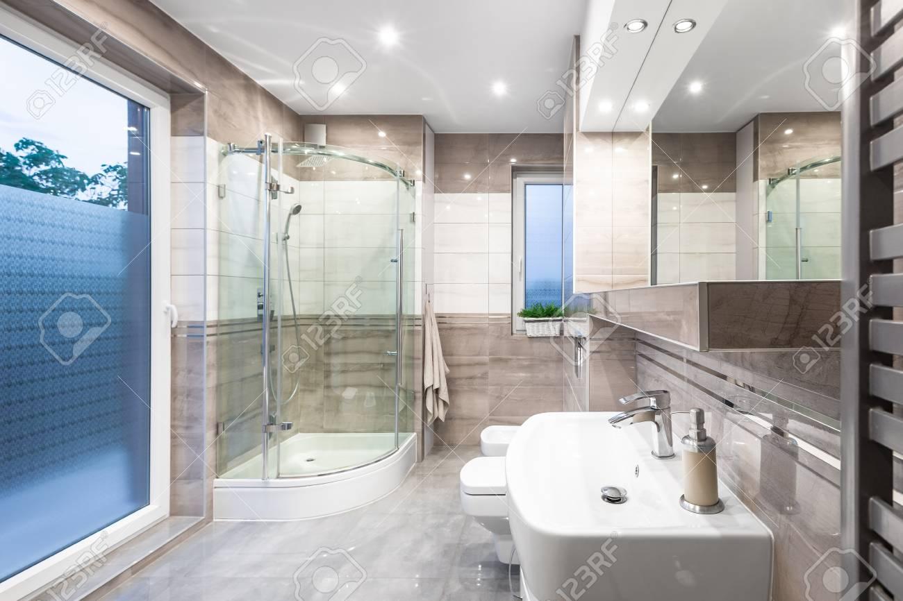 Nouvelle salle de bain design en blanc et beige avec fenêtre, douche à  l\'italienne, lavabo et grand miroir