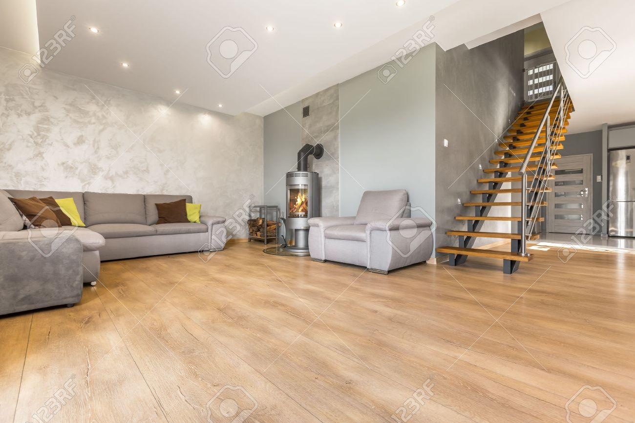 Spacieux salon ouvert avec un grand canapé d\'appoint, cheminée, plâtre  vénitien et un escalier en bois