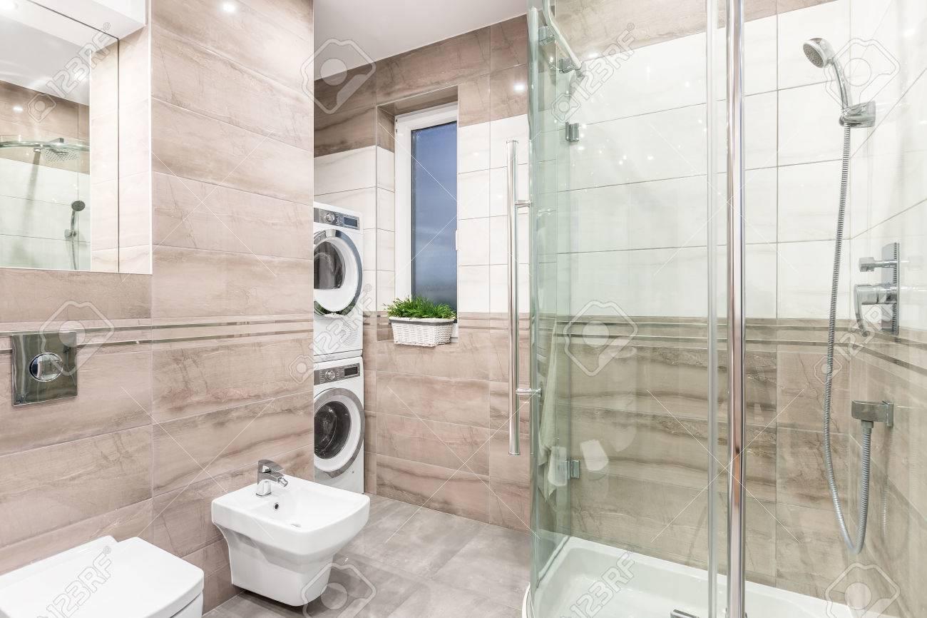 Salle de bains spacieuse beige avec miroir, toilette, bidet, grande douche,  machine à laver et sèche-linge