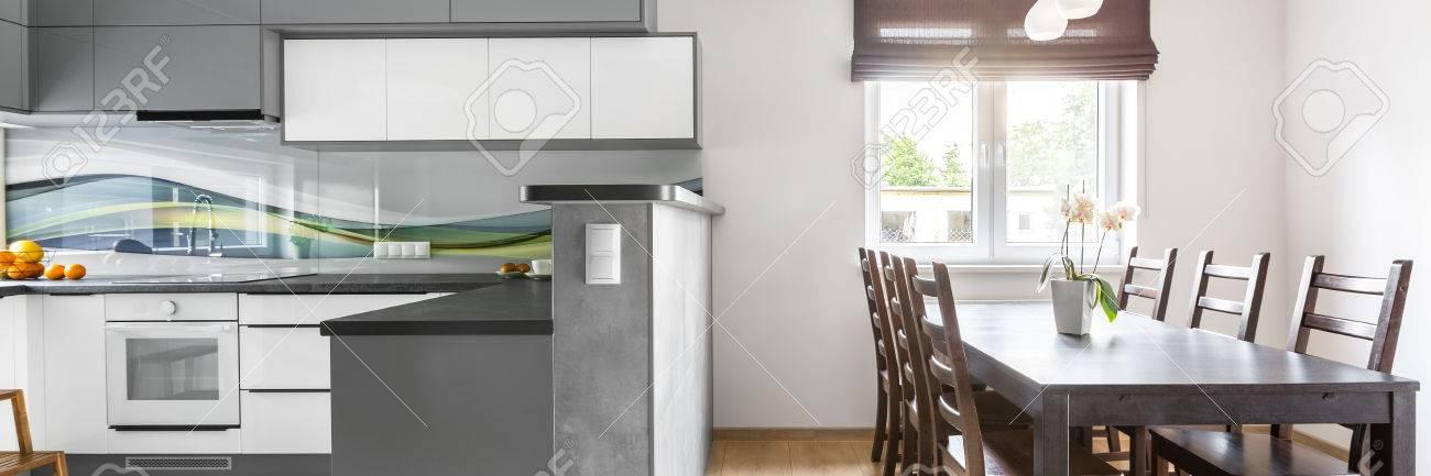 Panorama de l\'intérieur de la maison moderne avec cuisine spacieuse et  lumineuse ouverte sur coin repas avec fenêtre