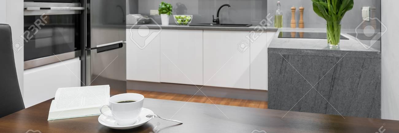 Panorama di tazza di caffè sul tavolo da pranzo in legno in bianco, cucina  moderna