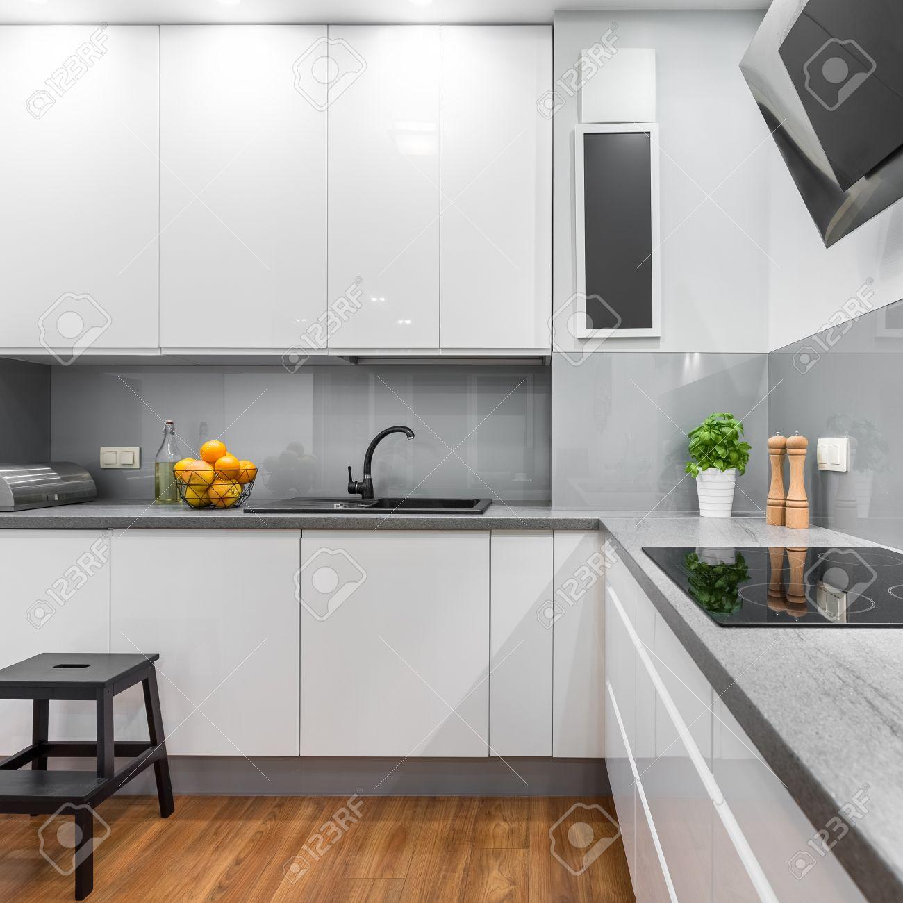 Cocina con muebles de color blanco, taburete de madera y encimera de  inducción