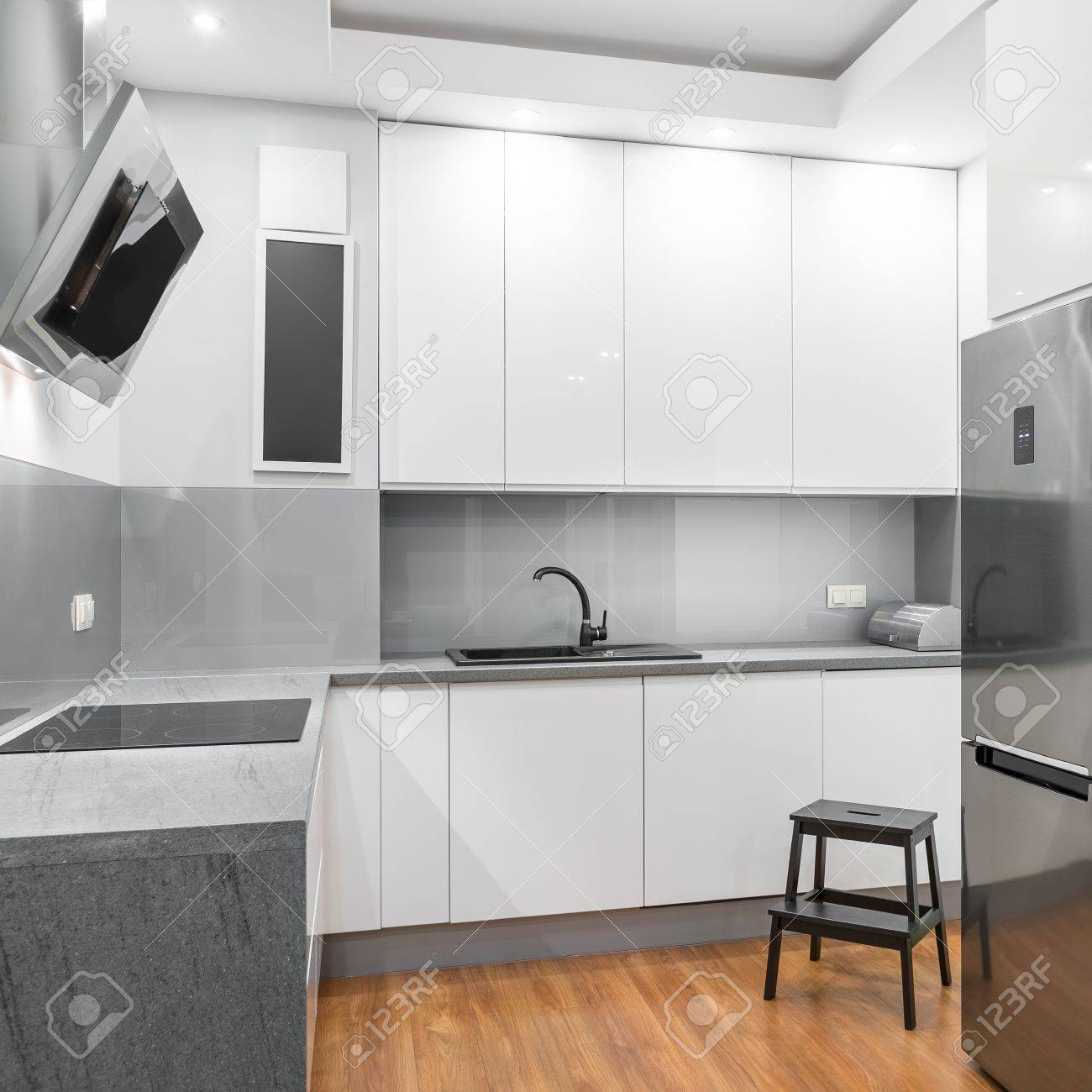 Functional white kitchen with wooden step stool, silver fridge..